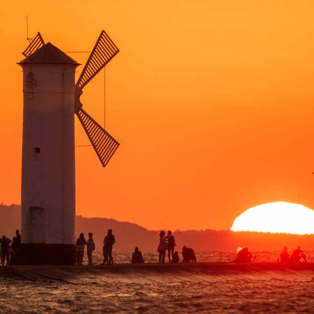 """lighthouse in the shape of a windmill in Swinoujscie in Poland during sunset"" stock image"