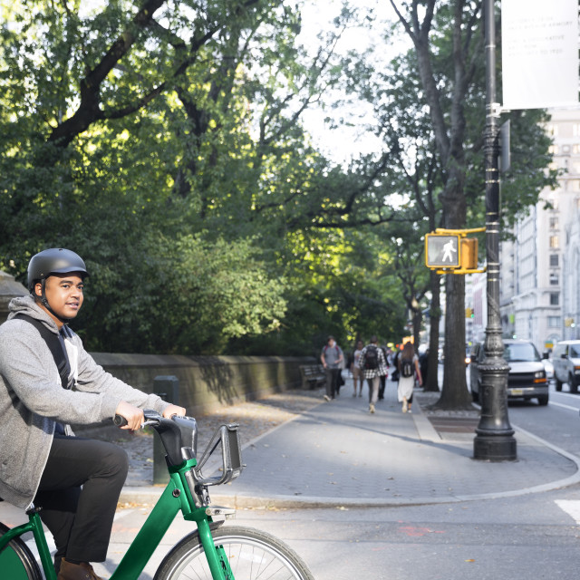 """Man looking away while riding bicycle on city street"" stock image"