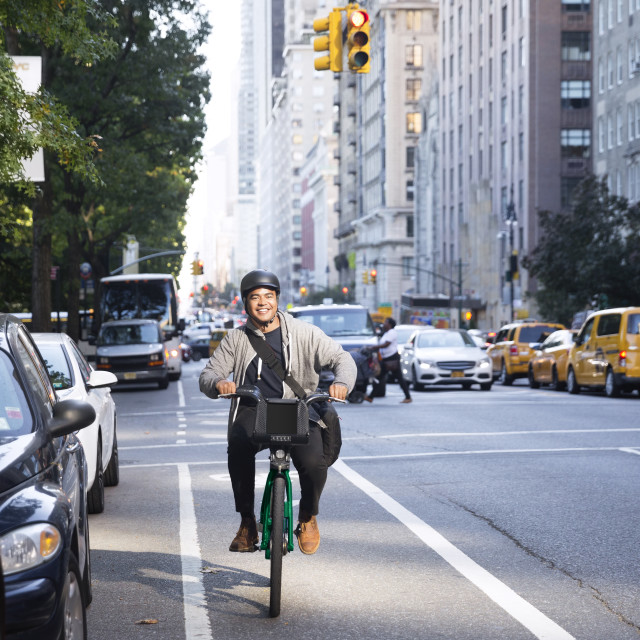 """Happy man riding bicycle on city street"" stock image"