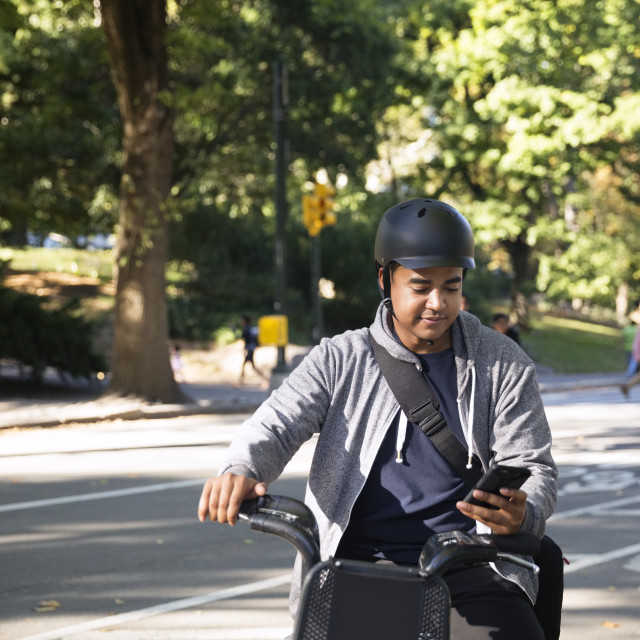 """Man using mobile phone while riding bicycle on city street"" stock image"
