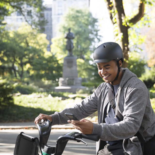 """Smiling man using mobile phone while riding bicycle on city street"" stock image"