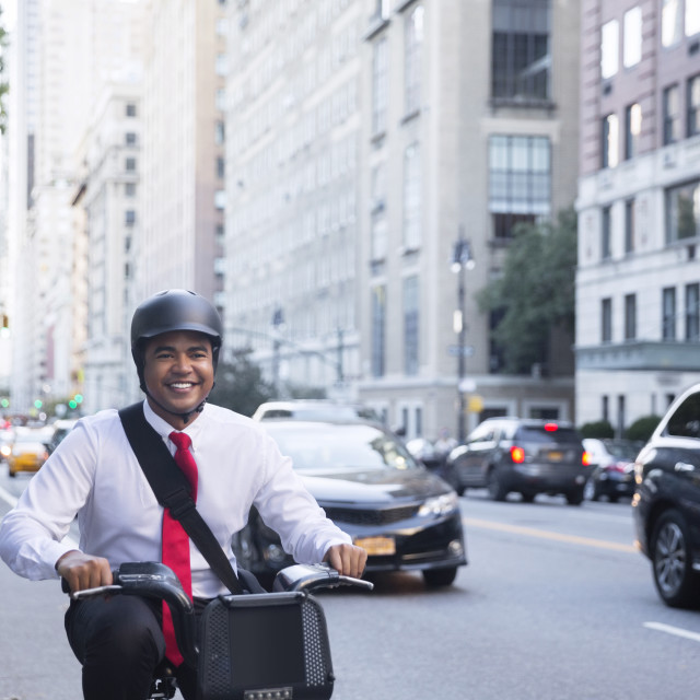 """Businessman riding bicycle on city street"" stock image"