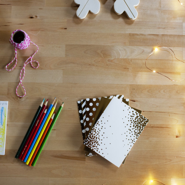 """High angle view of stationery with illuminated fairy lights on wooden table"" stock image"