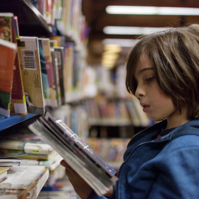 """""""Side view of boy reading comic book in library"""" stock image"""