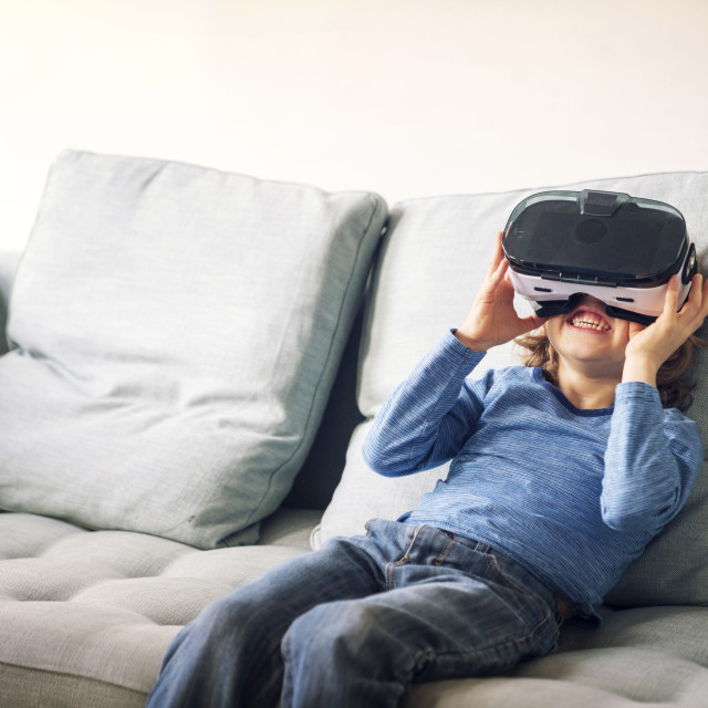 """Happy boy wearing virtual reality simulator sitting on sofa at home"" stock image"