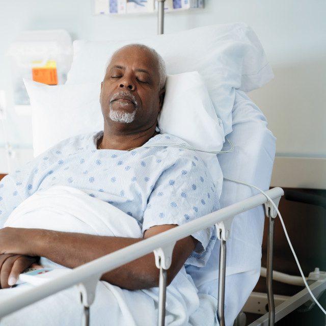 """Senior patient sleeping on bed in hospital ward"" stock image"
