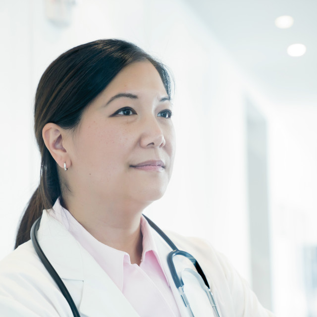 """""""Thoughtful female doctor looking away in hospital"""" stock image"""