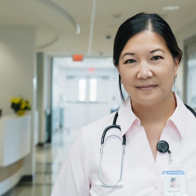 """""""Portrait of confident female doctor with stethoscope in hospital lobby"""" stock image"""