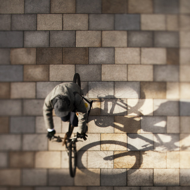 """Overhead view of man riding bicycle on street"" stock image"