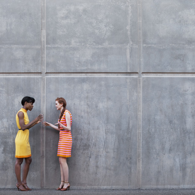 """Full length of multi-ethnic friends talking while standing against wall"" stock image"
