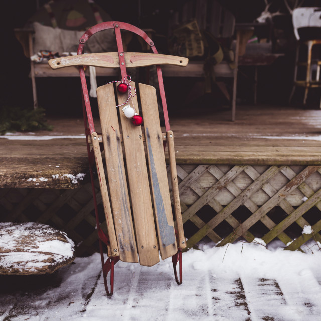"""Wooden sledge with baubles on porch during Christmas"" stock image"