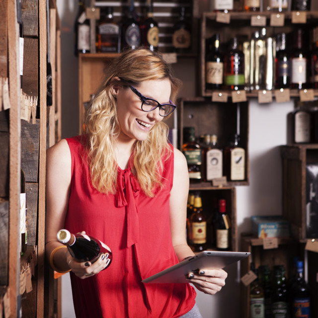 """""""Happy female entrepreneur using tablet computer while holding wine bottle in..."""" stock image"""