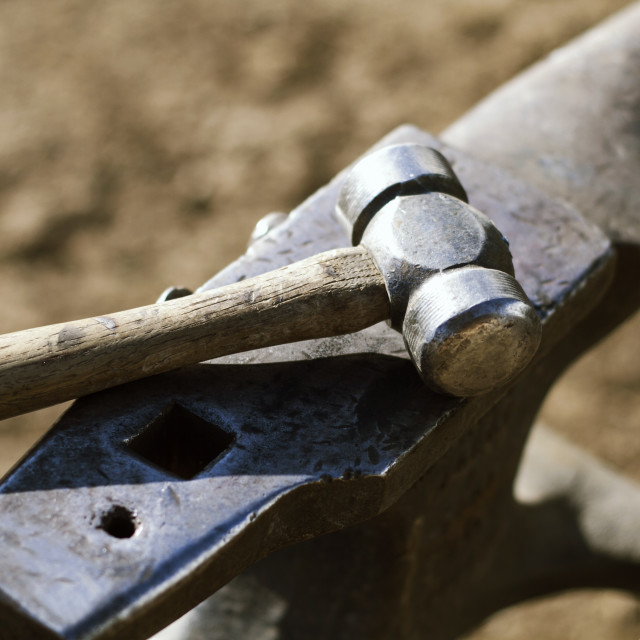 """""""High angle view of hammer and anvil on field"""" stock image"""