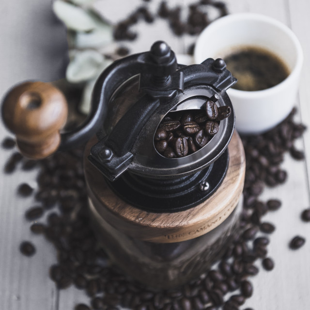 """""""Overhead view of grinder with roasted coffee beans on table"""" stock image"""
