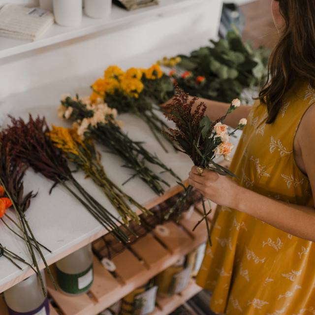"""""""High angle view of florist making bouquet at flower shop"""" stock image"""