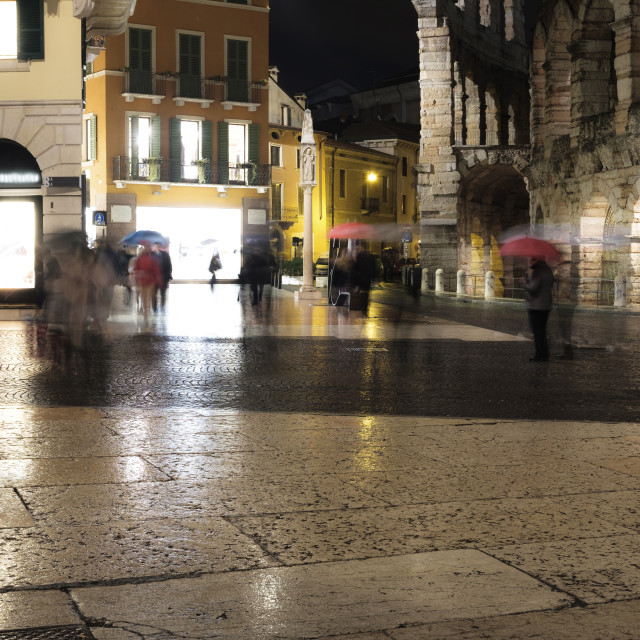 """Blurred motion of people with umbrella in illuminated city during rainfall at..."" stock image"