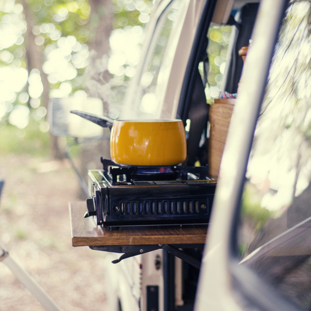 """""""Food prepared in saucepan on stove in travel trailer at forest"""" stock image"""