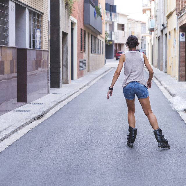 """Rear view of teenage girl inline skating on road amidst buildings"" stock image"
