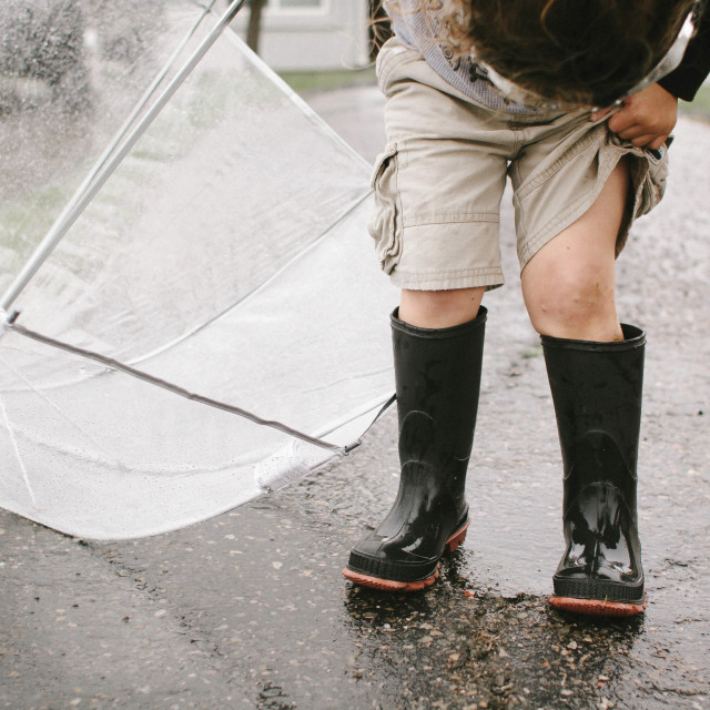 """""""Girl in rubber boots holding umbrella while standing on wet road"""" stock image"""
