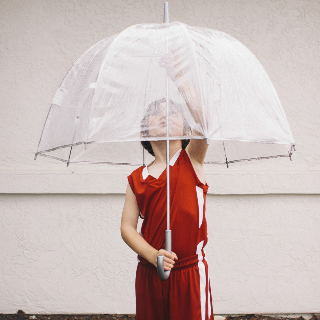 """""""Boy holding umbrella while standing against white wall"""" stock image"""