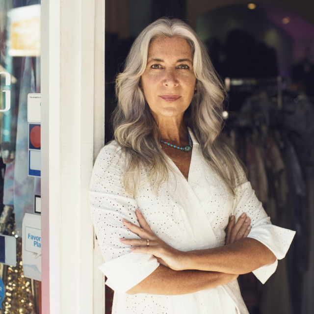 """""""Portrait of female entrepreneur standing arms crossed at the entrance of..."""" stock image"""