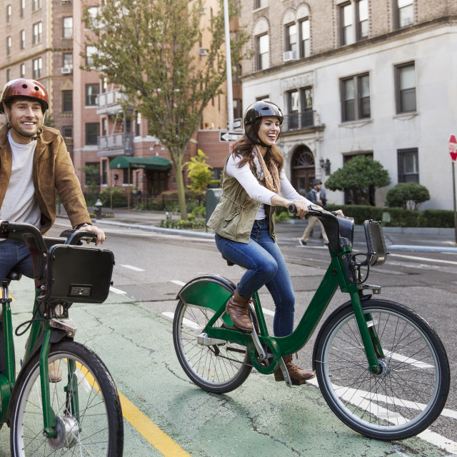 """Happy couple riding bicycle on city street"" stock image"
