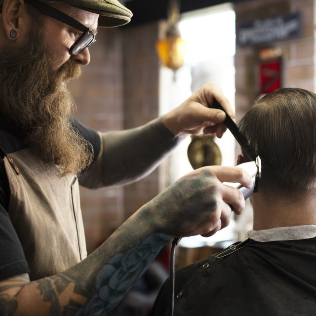 """""""Barber cutting man's hair with electric razor in shop"""" stock image"""