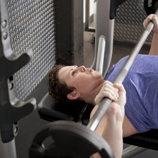 """High angle view of woman lifting barbells while lying on bench in gym"" stock image"