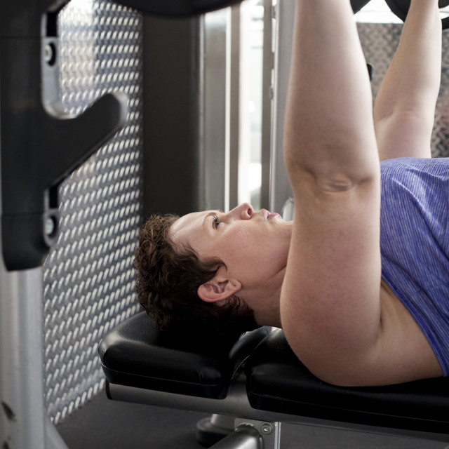"""Side view of woman lifting barbells while lying on bench in gym"" stock image"