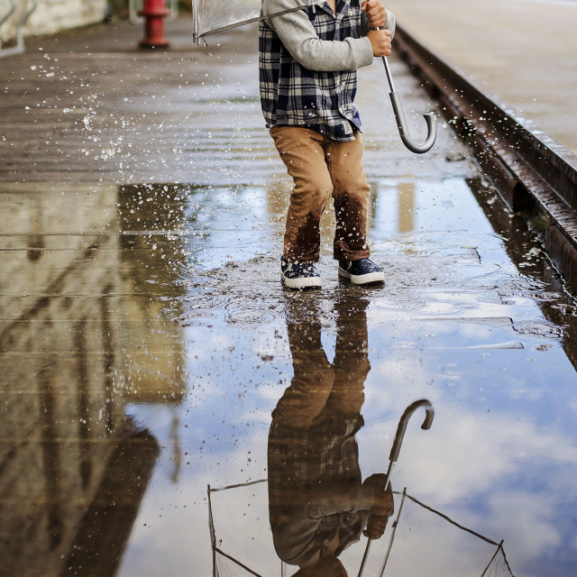 """Playful boy with umbrella jumping on puddle at street"" stock image"