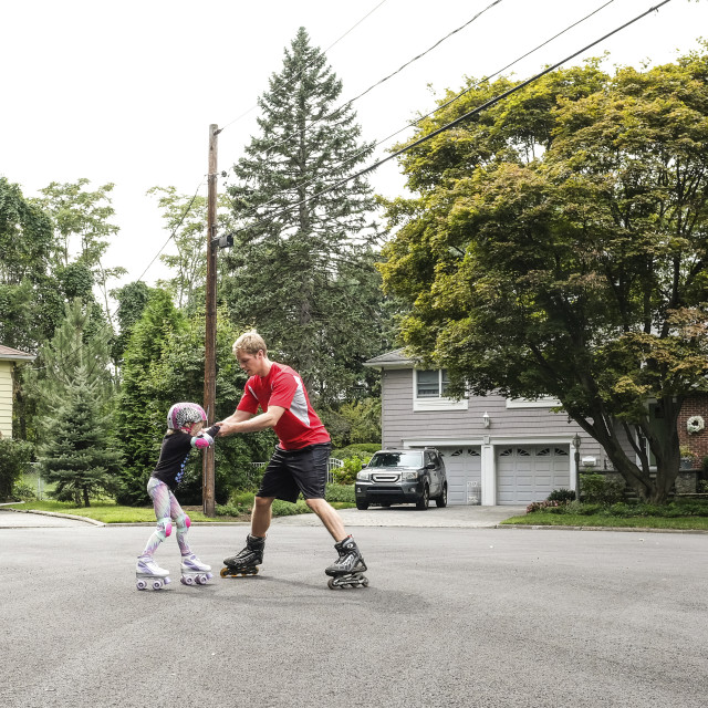 """Father teaching daughter to inline skate on road"" stock image"