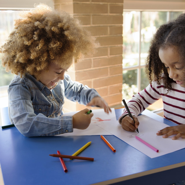 """""""Sisters drawing on papers at table"""" stock image"""
