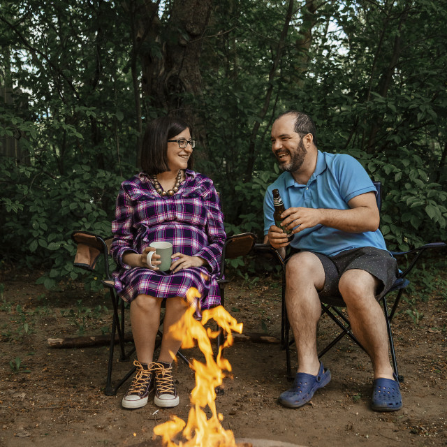"""""""Full length of happy couple sitting on camping chairs by campfire at forest"""" stock image"""