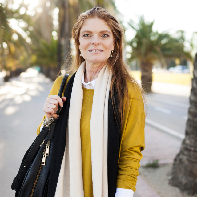 """""""Portrait of confident mature woman with purse standing in city"""" stock image"""