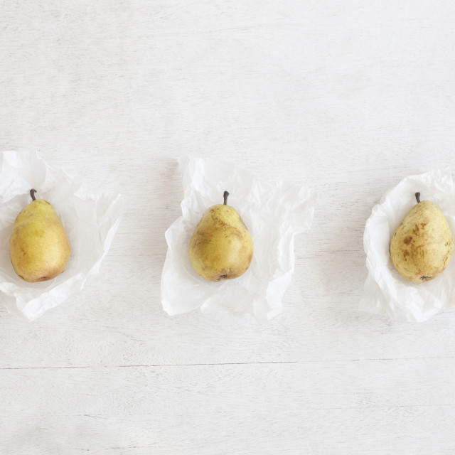 """""""Overhead view of pears in wax papers arranged on wooden table"""" stock image"""