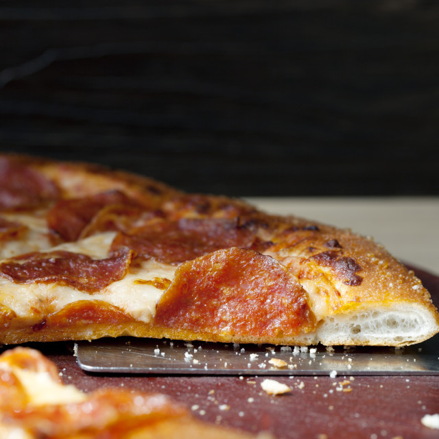 """""""Close-up of spatula in pizza on table"""" stock image"""