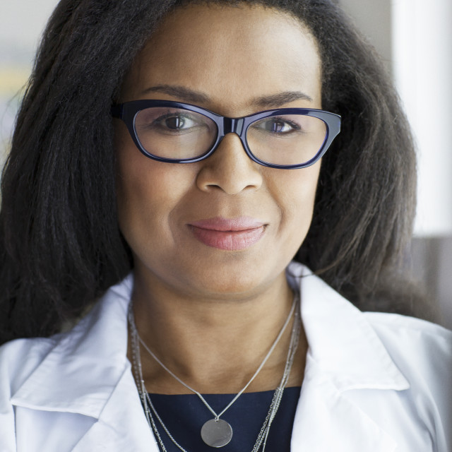 """""""Portrait of confident female doctor wearing eyeglasses while standing in..."""" stock image"""