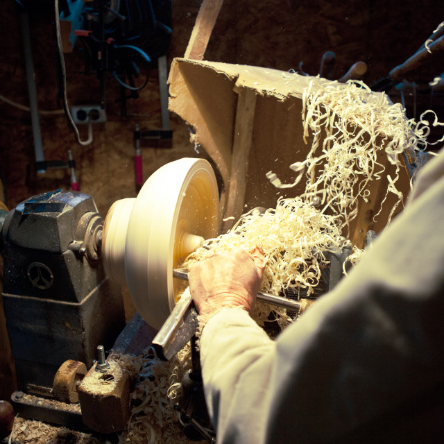 """Cropped image of carpenter carving wood on lathe machine at workshop"" stock image"