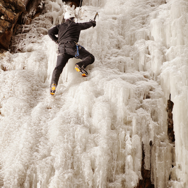"""""""Man climbing frozen waterfall against rock formation"""" stock image"""