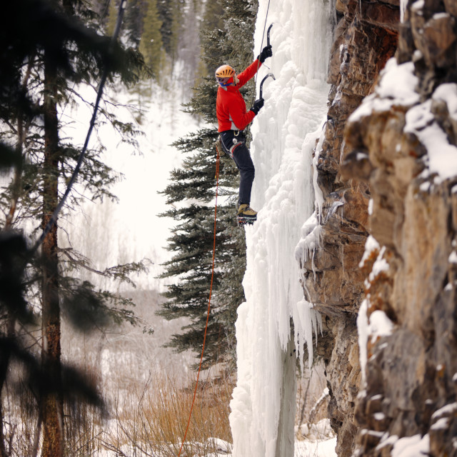 """""""Low angle view of hiker climbing frozen waterfall against rock formation"""" stock image"""