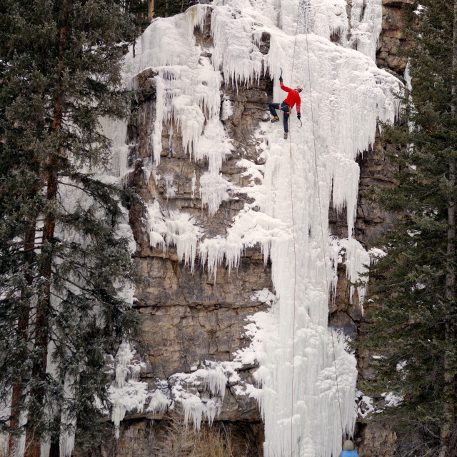 """""""Low angle view of man climbing frozen waterfall against trees"""" stock image"""