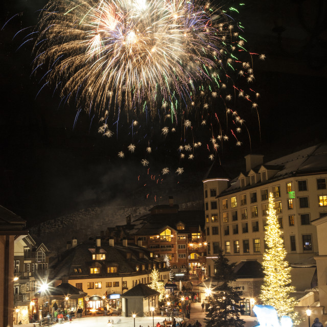 """""""Low angle view of firework display over illuminated city at night"""" stock image"""