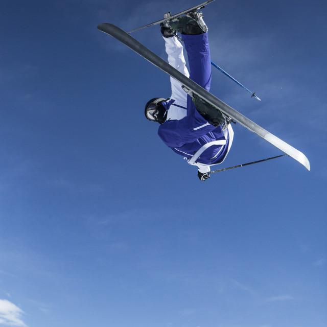 """""""Low angle view of skier in mid-air against blue sky"""" stock image"""