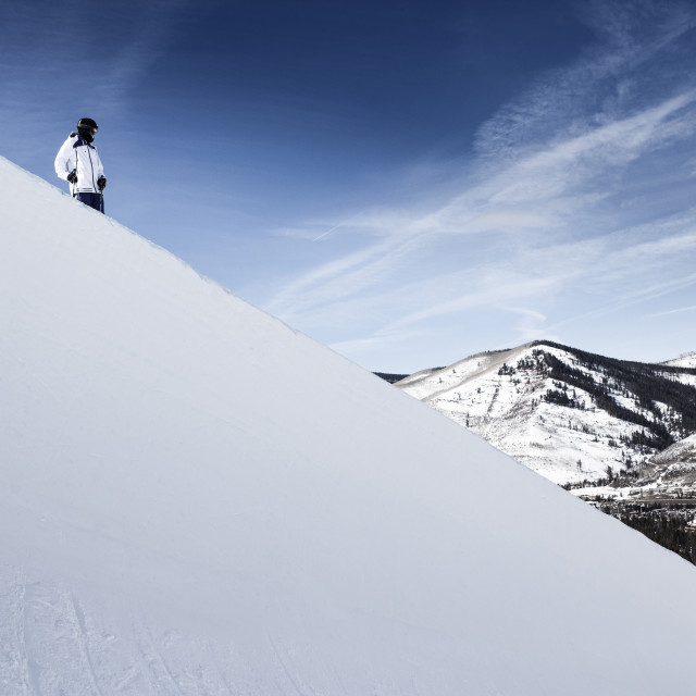 """""""Low angle view of skier standing on snow covered mountain against sky"""" stock image"""