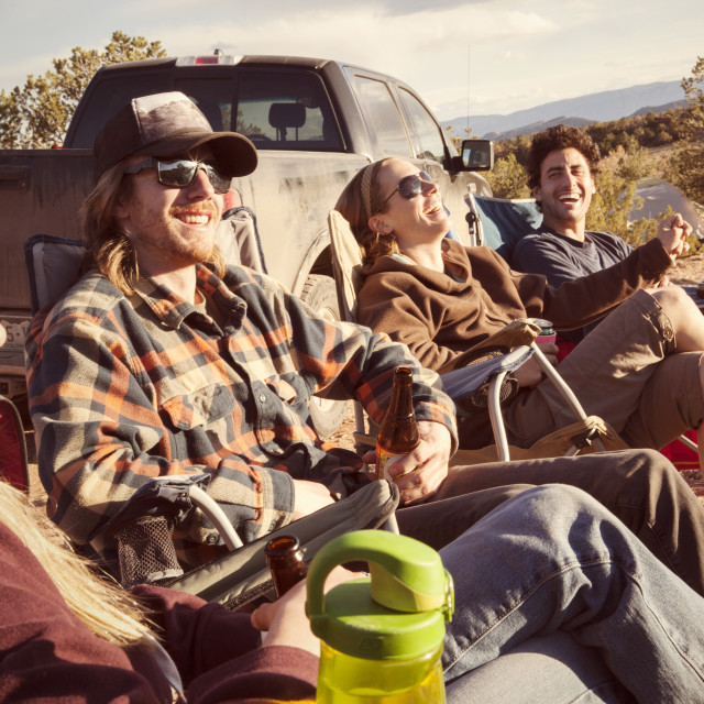 """""""Friends enjoying while resting against off-road vehicle at campsite"""" stock image"""