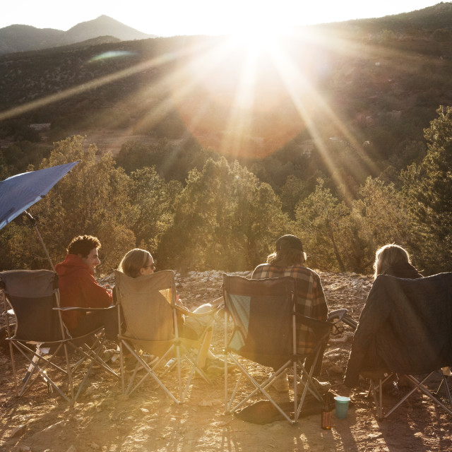 """""""Friends enjoying while resting at campsite against trees on sunny day"""" stock image"""