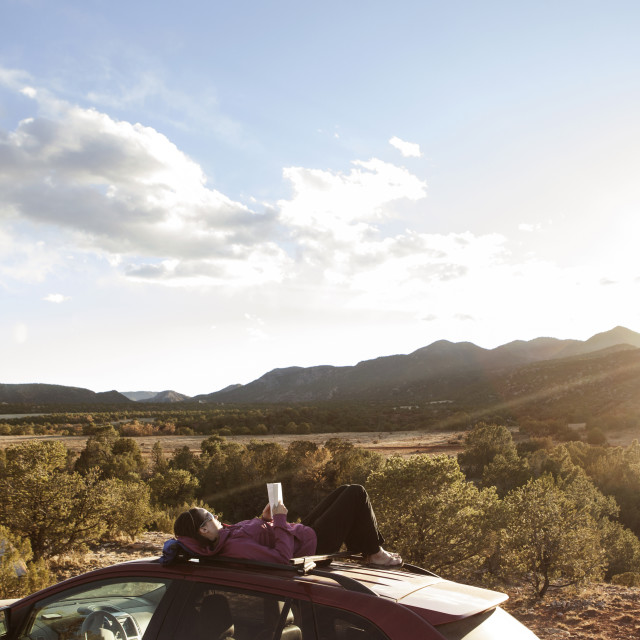 """""""Woman reading book while lying on car hood against mountain during sunny day"""" stock image"""