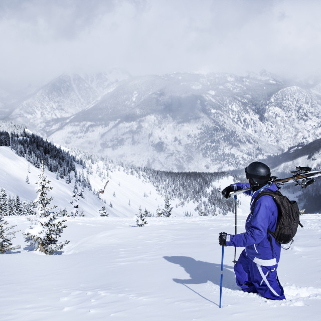 """""""Skier walking on snow covered mountain against sky"""" stock image"""