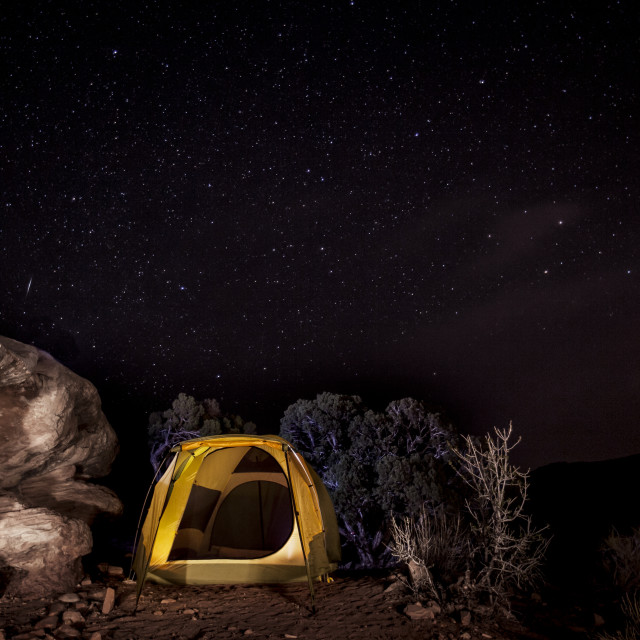 """""""Tent by rock on mountain against starry sky"""" stock image"""
