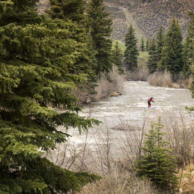 """""""Distant view of paddler paddling in river"""" stock image"""